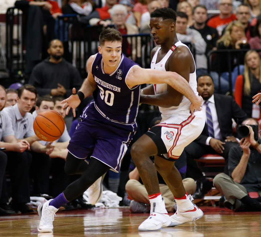 . Northwestern\'s Bryant McIntosh, left, tries to dribble around Ohio State\'s Jai\'Sean Tate during the second half of an NCAA college basketball game, Sunday, Jan. 22, 2017, in Columbus, Ohio. Northwestern defeated Ohio State 74-72. (AP Photo/Jay LaPrete)