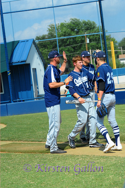 Hunter Heath gets congratulated by Coach Hawk and teammates after crossing home plate.