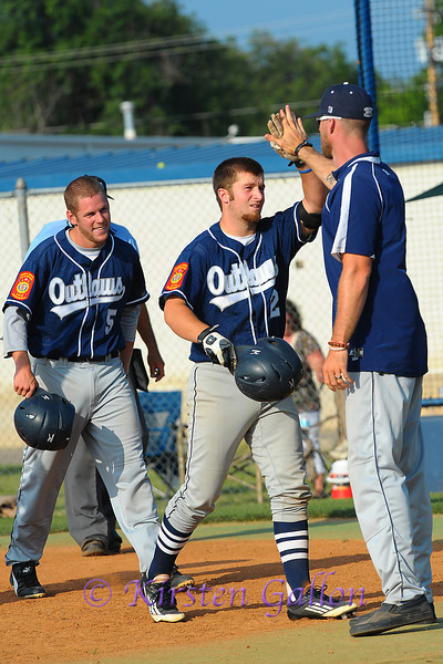 Taylor Hawkins gets a high five from Coach Shane Hawk after his home run.