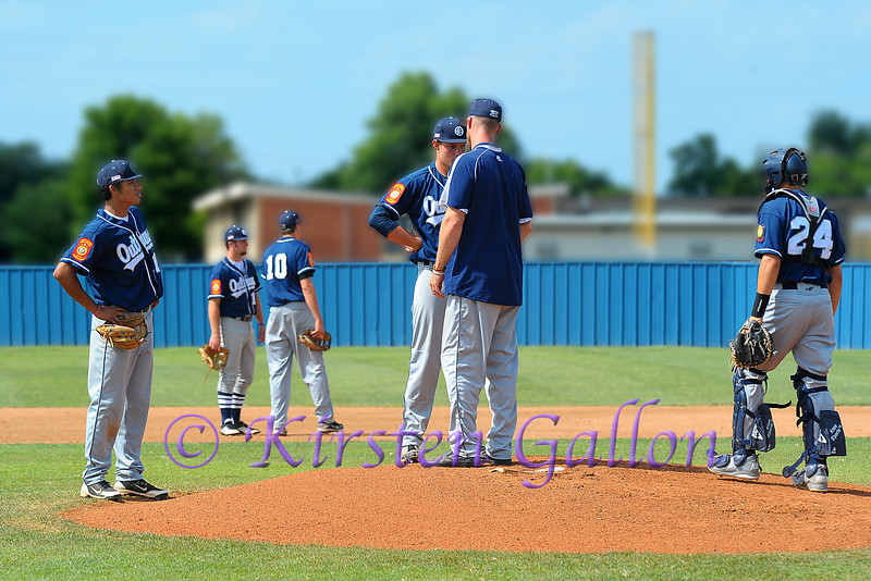 Coach Shane Hawk goes to the mound for a little motivational talk with pitcher Joel Davis.