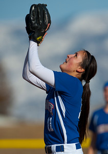 Fremont's Jessica Clark #11 concentrates on the pop fly. She catches the ball for a out. Plain City at Fremont High School on March 5, 2015
