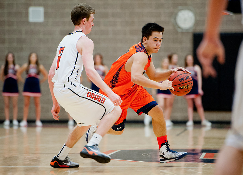 Jalen Tiev crosses mid-court as defender Cale Kwallek #2. press defense. At Ogden High School. On January 7 2015.