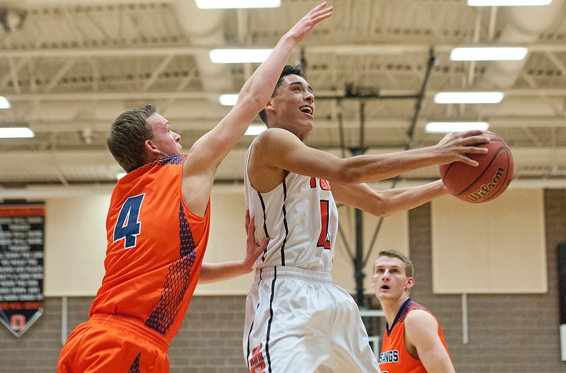 Nick Crowton #4 from Ogden High tries to shoot the ball underneath while Sam Adams #4 swats at the ball.  At Ogden High School. On Wednesday January 7 2015.