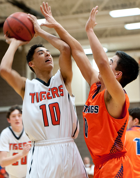 Ogden's Jaxon Clarke #10 takes a contested shot by Jalen Tiev #0. At Ogden High School. On January 7 2015.