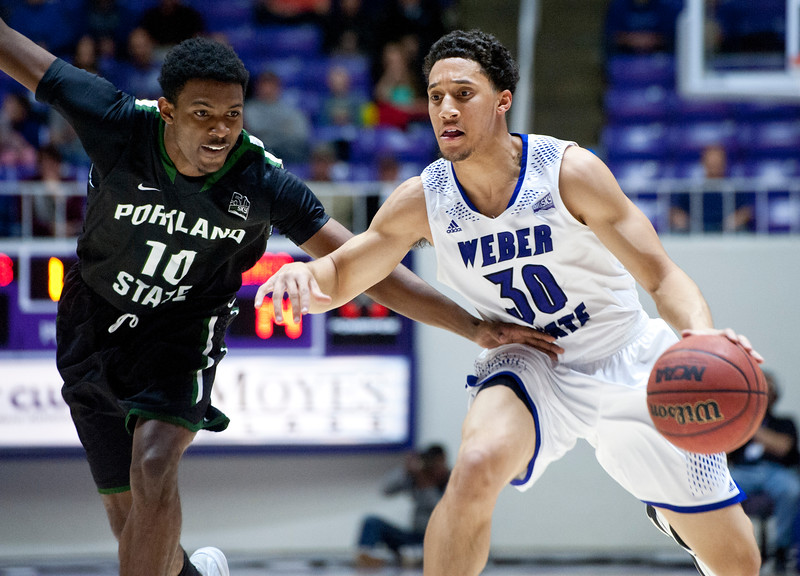 Portland's Izaiahiah Sweeney tires to steel the ball from Weber State's Jeremy Senglin # 30. At the Dee Event Center In Ogden on January 22, 2015.