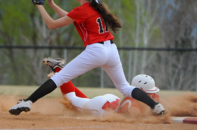 Bailee Trapp # 3 slides back into first base after her team mates ball was caught out. At Weber High School in Pleasant View on March 17, 2015.