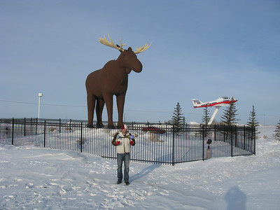 Caleb in his red mittens in from of Mac the Moose in Moose Jaw