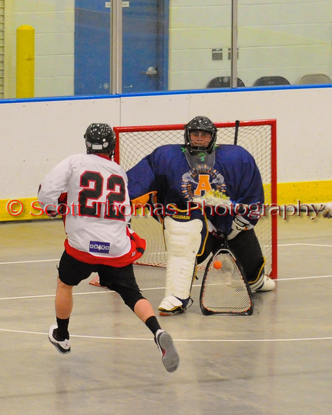 Allegany Arrows goalie Jake George (30) makes a stick save on Onondaga Redhawks Vince Thomas (22) at the Onondaga Nation Arena near Nedrow, New York on Saturday, May 3, 2014.  Onondaga won 21-5.