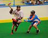 Onondaga Redhawks Matt Noble (18) is stick checked by Six Nations Slash Paul Gilligan (67) at the Onondaga Nation Arena near Nedrow, New York on Sunday, June 29, 2014.  Onondaga won 30-6.
