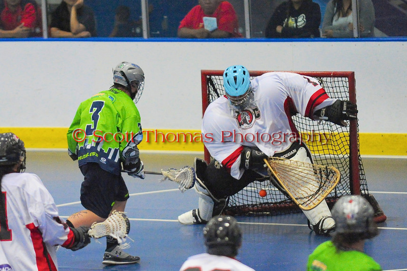 "Rochester Greywolves Craig Marvin (3) scores against  Onondaga Red Hawks goalie Spencer Lyones (1) in Can-Am Senior ""B"" Box Lacrosse playoff action at the Onondaga Nation Arena in Nedrow, New York on Friday, July 15, 2011.  Greywolves won 12-8."