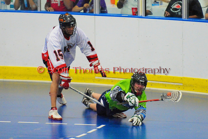 """Rochester Greywolves Sean Gilles (24) is checked by Onondaga Red Hawks Grant Bucktooth (15) in Can-Am Senior """"B"""" Box Lacrosse playoff action at the Onondaga Nation Arena in Nedrow, New York on Friday, July 15, 2011.  Greywolves won 12-8. Players 15 & 24."""