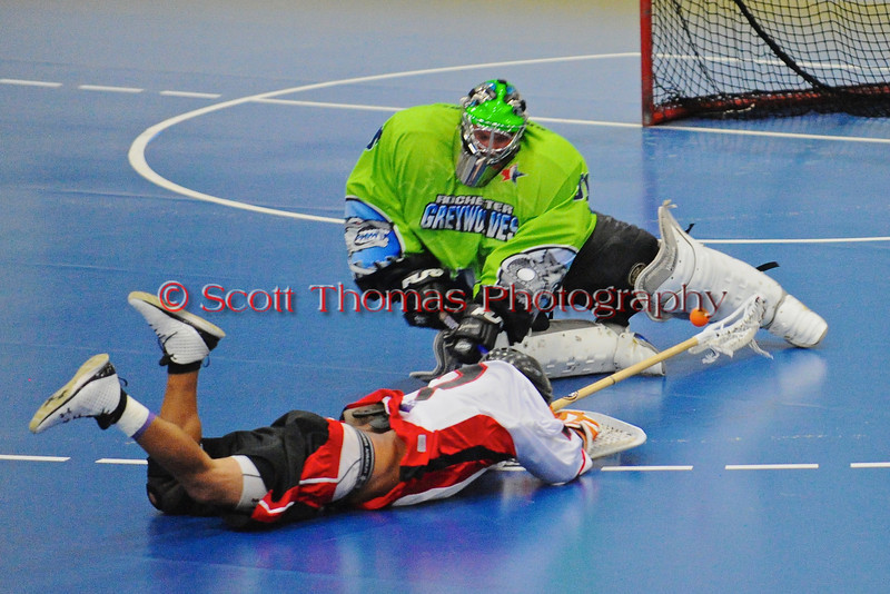 """Rochester Greywolves goalie Cory Bazylewski (00) and  Onondaga Red Hawks Mike Abrams (7) go after a loose ball in Can-Am Senior """"B"""" Box Lacrosse playoff action at the Onondaga Nation Arena in Nedrow, New York on Friday, July 15, 2011.  Greywolves won 12-8."""