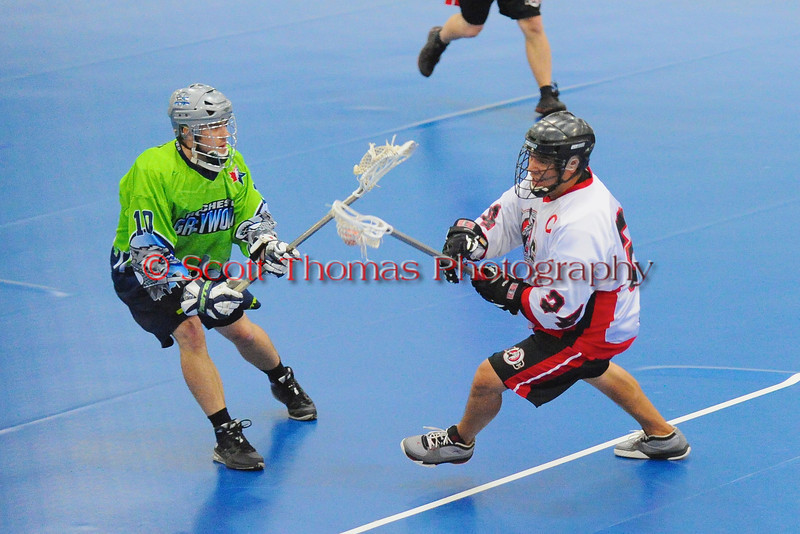 """Onondaga Red Hawks captain David Stout (24) makes a move on Rochester Greywolves Mike Lachute (10) in Can-Am Senior """"B"""" Box Lacrosse playoff action at the Onondaga Nation Arena in Nedrow, New York on Friday, July 15, 2011.  Greywolves won 12-8."""