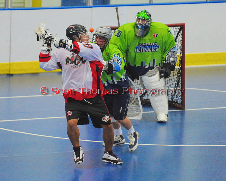 """Onondaga Red Hawks Pete Benedict (10) shoots over his shoulder against the Rochester Greywolves in Can-Am Senior """"B"""" Box Lacrosse playoff action at the Onondaga Nation Arena in Nedrow, New York on Friday, July 15, 2011.  Greywolves won 12-8."""