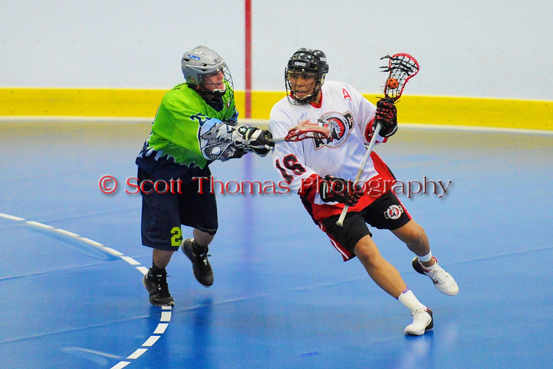 """Onondaga Red Hawks Neal Powless (16) being watched by Rochester Greywolves Steve Personale (29) in Can-Am Senior """"B"""" Box Lacrosse playoff action at the Onondaga Nation Arena in Nedrow, New York on Friday, July 15, 2011.  Greywolves won 12-8."""