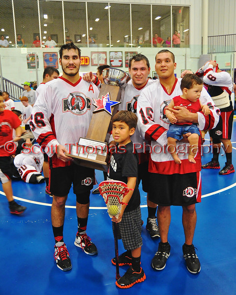 """Onondaga Redhawks Brett Bucktooth (66) and Grant Bucktooth (15) with their sons and the Stanley """"Butch"""" Jimerson Can-Am Lacrosse Champions Cup after defeating the Newtown Golden Eagles in the Can-Am Senior """"B"""" Box Lacrosse finals at the Onondaga Nation Arena near Nedrow, New York."""