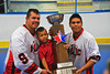 "Onondaga Redhawks Ron Cogan (9) and Kevin Wilkerson (8) posing with the Stanley ""Butch"" Jimerson Can-Am Lacrosse Champions Cup at the Onondaga Nation Arena near Nedrow, New York."