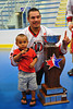 "Onondaga Redhawks David Stout (24) with his son posing with the Stanley ""Butch"" Jimerson Can-Am Lacrosse Champions Cup at the Onondaga Nation Arena near Nedrow, New York."