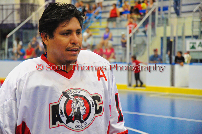 """Onondaga Redhawks Neal Powless (16) waiting to shake hands with the Newtown Golden Eagles after winning the Can-Am Senior """"B"""" Box Lacrosse finals at the Onondaga Nation Arena near Nedrow, New York."""