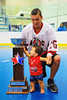 "Onondaga Redhawks Grant Bucktooth (15) and son posing with the Stanley ""Butch"" Jimerson Can-Am Lacrosse Champions Cup at the Onondaga Nation Arena near Nedrow, New York."