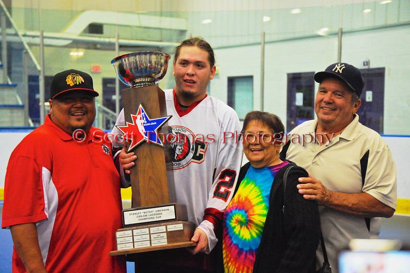 """Onondaga Redhawks James Cathers (22) posing with his family and the Stanley """"Butch"""" Jimerson Can-Am Lacrosse Champions Cup after defeating the Newtown Golden Eagles in the Can-Am Senior """"B"""" Box Lacrosse finals at the Onondaga Nation Arena near Nedrow, New York."""