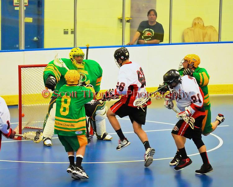 "Onondaga Redhawks Brett Bucktooth (66) scores against the Newtown Golden Eagles in a Can-Am Senior ""B"" box lacrosse game at the Onondaga Nation Arena (Tsha'hon'nonyen'dakhwa') near Nedrow, New York on Saturday, May 12, 2012."