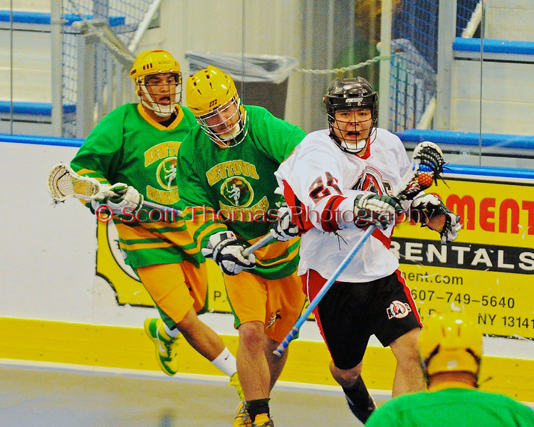 """Onondaga Redhawks Junior Bucktooth (25) escapes the Newtown Golden Eagles defenders in a Can-Am Senior """"B"""" box lacrosse game at the Onondaga Nation Arena (Tsha'hon'nonyen'dakhwa') near Nedrow, New York on Saturday, May 12, 2012."""