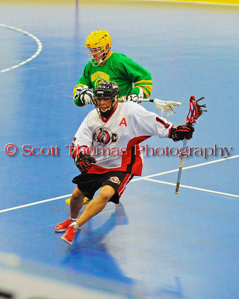 "Onondaga Redhawks Neal Powless (16) avoiding a Newtown Golden Eagles defender late in the third period in a Can-Am Senior ""B"" box lacrosse game at the Onondaga Nation Arena (Tsha'hon'nonyen'dakhwa') near Nedrow, New York on Saturday, May 12, 2012."