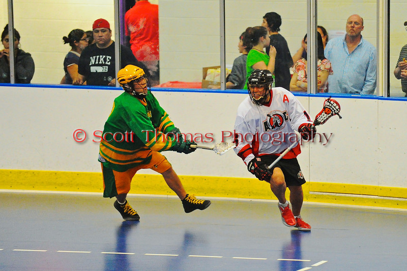"""Onondaga Redhawks Neal Powless (16) looking to make a play against the Newtown Golden Eagles in a Can-Am Senior """"B"""" box lacrosse game at the Onondaga Nation Arena (Tsha'hon'nonyen'dakhwa') near Nedrow, New York on Saturday, May 12, 2012."""