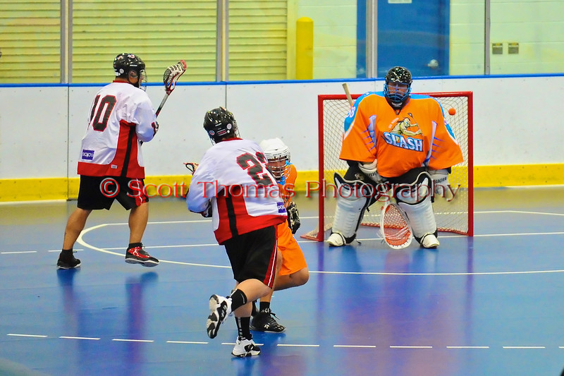 """Onondaga Redhawks James Cathers (22) threads the needle to score against the Six Nations Slash in game three of the second round of the Can-Am Senior """"B"""" playoffs at the Onondaga Nation Arena near Nedrow, New York on Sunday, July 29, 2012. Redhawks won 15 to 6."""