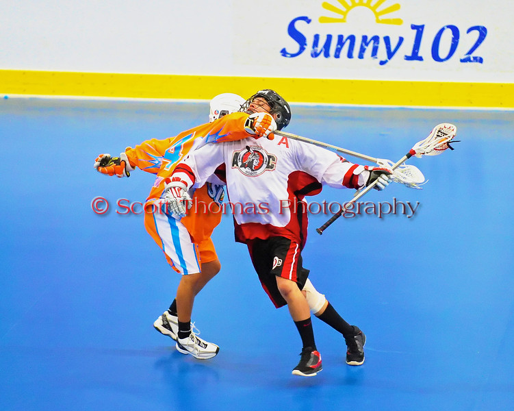"""Onondaga Redhawks Dustin Hill (20) gets clotheslined by Six Nations Slash Russell Longboat (24) in round two of the Can-Am Senior """"B"""" playoffs at the Onondaga Nation Arena near Nedrow, New York on Friday, July 27, 2012. Redhawks won 17 to 5."""