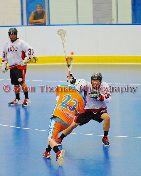 """Six Nations Slash Jeff VanEvery (23) fires a shot over Onondaga Redhawks defender Kevin Bucktooth (25) in round two of the Can-Am Senior """"B"""" playoffs at the Onondaga Nation Arena near Nedrow, New York on Friday, July 27, 2012. Redhawks won 17 to 5."""