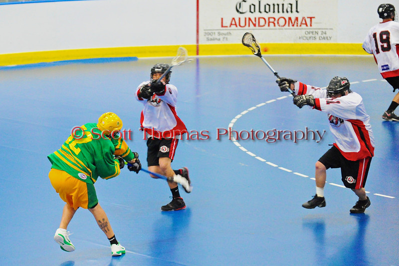 """Newtown Golden Eagles Preston Lay (52) fires a shot past Onondaga Redhawks defenders in the finals of the Can-Am Senior """"B"""" Lacrosse league at the Onondaga Nation Arena near Nedrow, New York."""