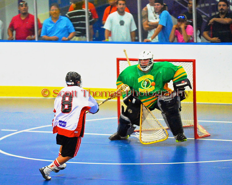 """Onondaga Redhawks Kevin Wilkerson (8) puts a shot on goal against the Newtown Golden Eagles in the finals of the Can-Am Senior """"B"""" Lacrosse league at the Onondaga Nation Arena near Nedrow, New York."""