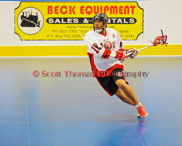 """Onondaga Redhawks Neal Powless (16) lining up a shot against the Newtown Golden Eagles in the Can-Am Senior """"B"""" Box Lacrosse finals at the Onondaga Nation Arena near Nedrow, New York."""