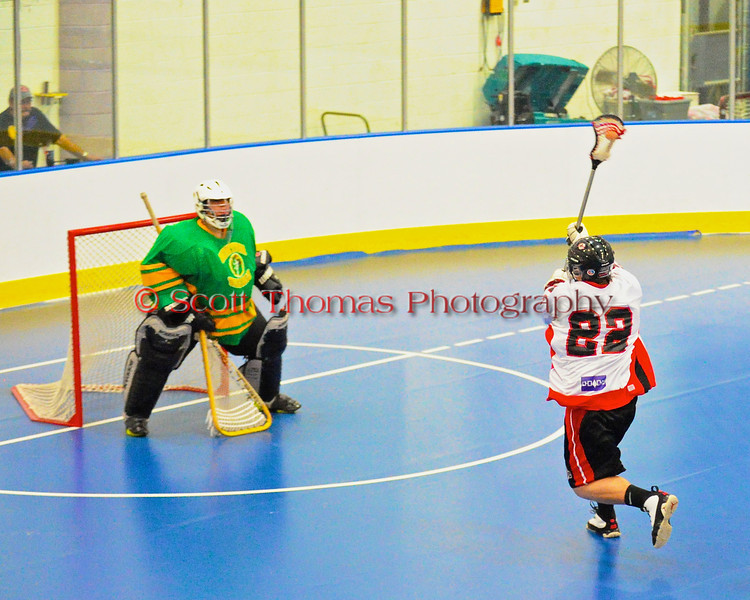 "Onondaga Redhawks James Cathers (22) closes in on the Newtown Golden Eagles netminder in the Can-Am Senior ""B"" Box Lacrosse finals at the Onondaga Nation Arena near Nedrow, New York."