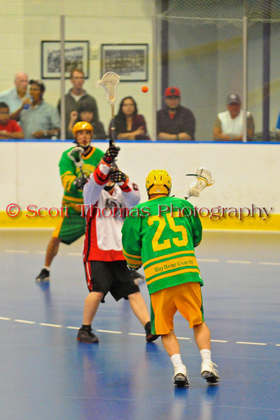"""Newtown Golden Eagles Tracy White (25) passes over an Onondaga Redhawks player in the Can-Am Senior """"B"""" Box Lacrosse finals at the Onondaga Nation Arena near Nedrow, New York."""