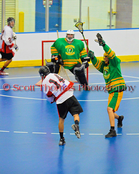 "Onondaga Redhawks Tyler Hill (14) shoots and scores against the Newtown Golden Eagles in the Can-Am Senior ""B"" Box Lacrosse finals at the Onondaga Nation Arena near Nedrow, New York."