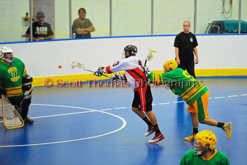 """Onondaga Redhawks Dwayne Porter (23) leans in for a shot on goal against the Newtown Golden Eagles in the finals of the Can-Am Senior """"B"""" Lacrosse league at the Onondaga Nation Arena near Nedrow, New York."""