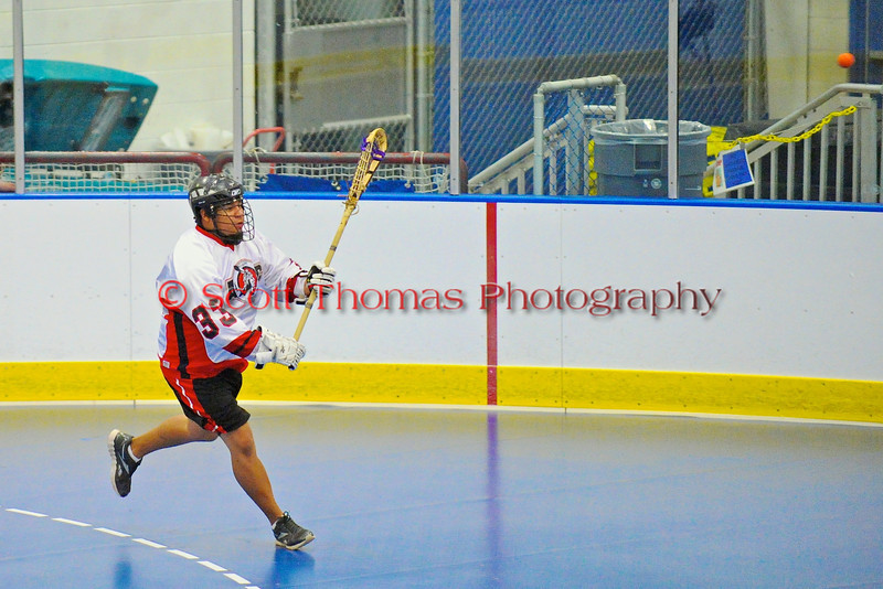 """Onondaga Redhawks Murray Stout Jr. (33) passes out of his end against the Rochester Greywolves in Can-Am Senior """"B"""" Box Lacrosse at the Onondaga Nation Arena near Nedrow, New York on Saturday, April 28, 2012."""