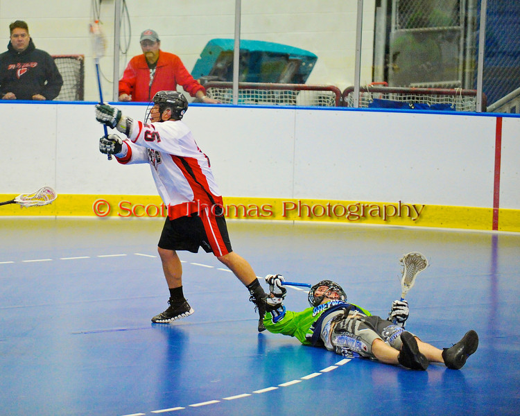 """Onondaga Redhawks """"Junior"""" Bucktooth (25) shots after eluding a Rochester Greywolves defender in Can-Am Senior """"B"""" Box Lacrosse at the Onondaga Nation Arena near Nedrow, New York on Saturday, April 28, 2012."""
