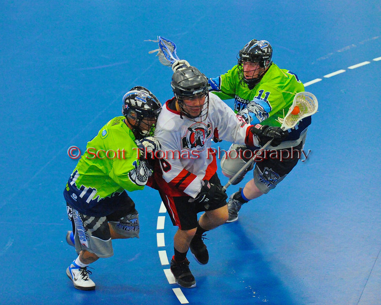 """Onondaga Redhawks Neal Pwoless (16) splitting two Rochester Greywolves players in Can-Am Senior """"B"""" Box Lacrosse at the Onondaga Nation Arena near Nedrow, New York on Saturday, April 28, 2012."""