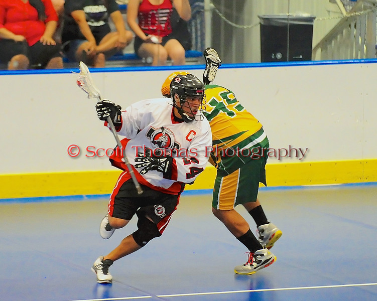 Onondaga Redhawks Dave Stout (24) sidesteps a Newtown Golden Eagles defender at the Onondaga Nation Arena near Nedrow, New York on Friday, July 5, 2013. Newtown won 10-9.