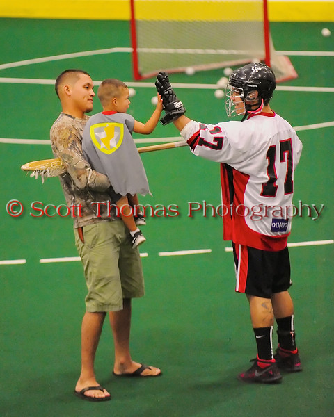 """Onondaga Redhawks Andy Jamerison (17) greets a young fan before playing the Newtown Golden Eagles in the Can-Am Senior """"B"""" Box Lacrosse finals at the Onondaga Nation Arena near Nedrow, New York on Saturday, August 2, 2014.  Onondaga won 11-5."""