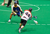Onondaga Redhawks Brian Phillips Jr. (44) fires a shot around an Allegany Arrows defender in Can-Am Box Lacrosse action at the Onondaga Nation Arena near Nedrow, New York on Saturday, May 14, 2016.  Onondaga won 17-5.
