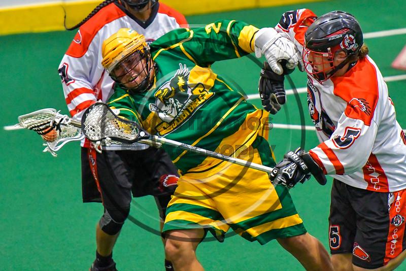 Onondaga Redhawks Cameron Simpson (5) checks a Newtown Golden Eagles player in Can-Am Box Lacrosse action at the Onondaga Nation Arena near Nedrow, New York on Saturday, July 9, 2016.  Onondaga won 14-6.