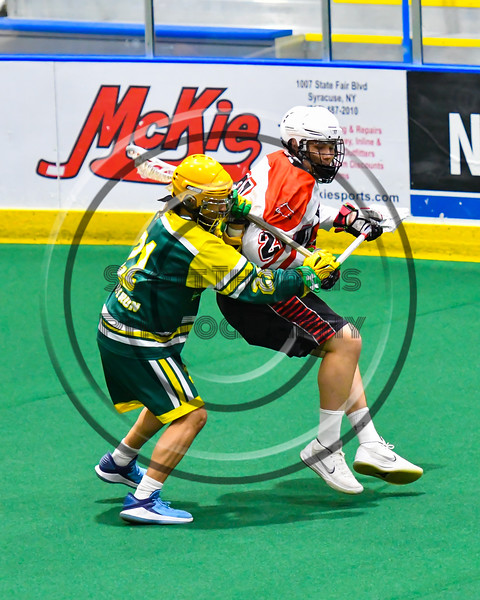Onondaga Redhawks Percy Booth (21) being defended by Newtown Golden Eagles Kaine Kettle (21) in Can-Am Box Lacrosse action at the Onondaga Nation Arena near Nedrow, New York on Sunday, April 28, 2019.  Onondaga won 8-6.