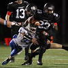 DAVID LE/Staff photo. Danvers junior Quintin Holland (33) reaches out and barely drags down Marblehead running back Jaason Lopez (23). 11/13/15.