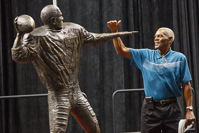 Marlin Briscoe sizes up his statue after the unveiling in Baxter Arena. UNO Basketball player Tra-Deon Hollins was the model for the statue.   Sept. 23, 2016