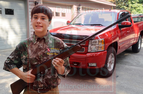 Matt Hamilton/The Daily Citizen<br /> Braxton Bates, 12, with his air rifle and 2013 Chevy Silverado extended cab Wednesday  in Chatsworth.